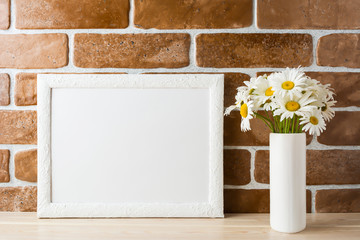 White landscape frame mockup with daisy bouquet in styled vase