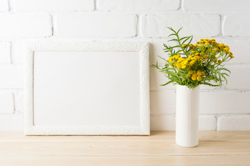 White landscape frame mockup with yellow flowers near painted brick walls
