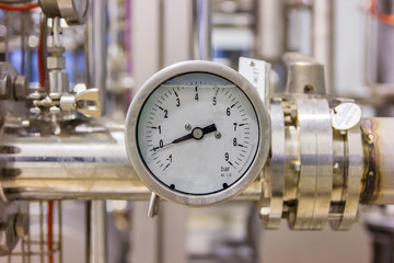 Closeup of pressure gauge, pressure gauge for monitor condition. Pipes and valves at pharmacy industry manufacture factory.