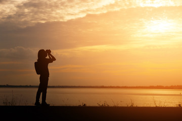 Silhouette woman shooting landscape photo