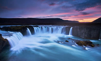 Stunning sunset over Godafoss Waterfall with smooth flowing in Iceland