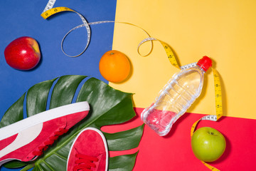 Sport concept. Fitness equipment. Sneakers, water, apple, dumbbell on colorful background.
