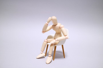 Wood mannequin on gray background Sit down and thinking