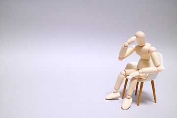 Wood mannequin on gray background Sit down and thinking Character space