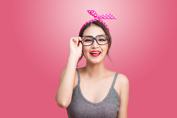 Fashion portrait of asian girl with sunglasses standing on pink background.