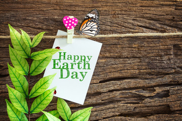Happy Earth Day paper note hanging by red heart clips on wooden background