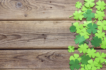 Paper clover leaves on the old wooden background. Space for text, top view.