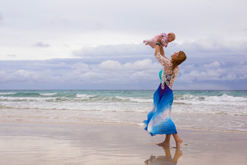 Mother holding her baby on the beach