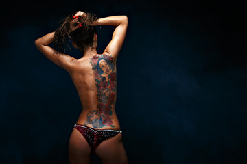 Back view of young topless woman showing a huge tattoo on her back on the black background.