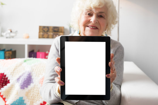 Senior woman showing tablet computer