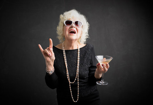 Cool grandmother with sunglasses and drink in hand