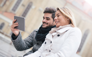 Couple in love sitting on the bench in the center of the city, having fun with tablet. Dating, lifestyle concept