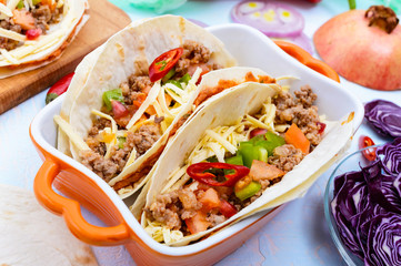 Spicy Mexican tacos with minced meat, mashed beans, vegetables, grated cheese.