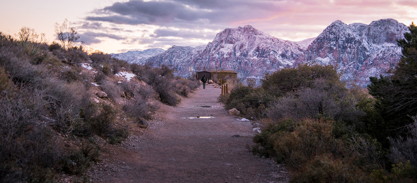 a Man backpack in the Redrock Canyon National Park with snow and sunset
