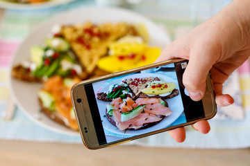 Smartphone taking picture from organic healthy sandwiches.