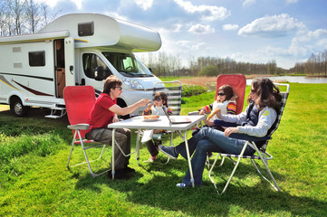 Family vacation, RV (camper) travel with kids, happy parents with children sit at the table in camping on holiday trip in motorhome