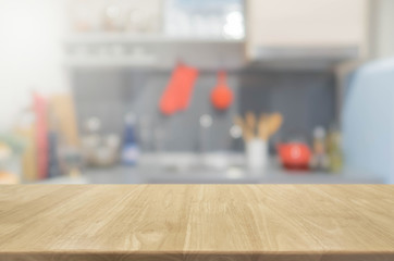 Wood table top and blurred kitchen interior background with vintage filter - can used for display or montage your products.