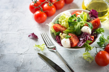 Fresh salad in a bowl. Green leaves tomatoes mozarella. Organic diet food