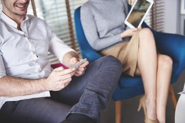 Business couple organizing things on wireless technology