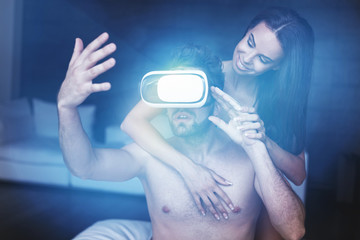 Young man playing virtual reality with headset and girlfriend with glowing light