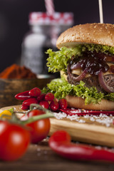 Home made burgers on wooden background.