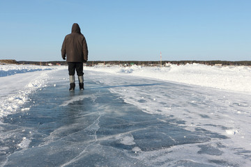 Man walking along a road of ice on the frozen reservoir in the winter, Ob River, Siberia, Russia