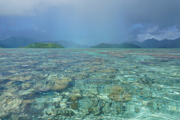 Pacific island lagoon, sunny weather on the water and cloud with rain on the islands, Huahine, French Polynesia