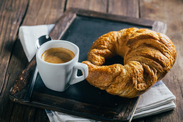 Espresso coffee cup and croissant on blank blackboard over wooden table