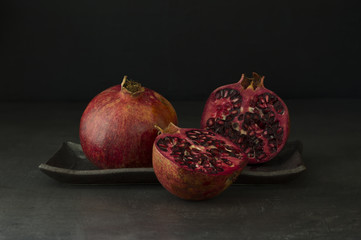 Two pomegranates, one sliced on a plate on a dark table top