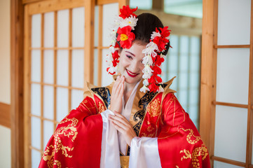 cosplay. beautiful, modest geisha in a red kimono posing in a Japanese house with a fan