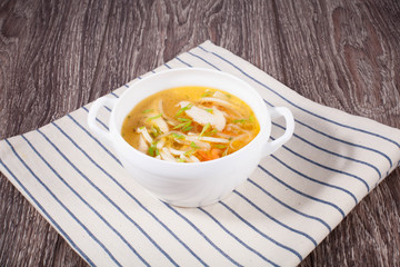 Chicken soup on a wooden background with a linen towel in a white tureen