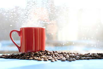spring mood with warming drink/ red cup of hot coffee on a background window with raindrops