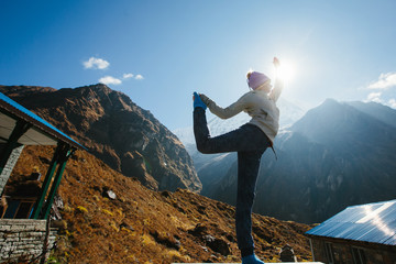 Young sport woman doing fitness exercise in tourist trekking on Himalaya mountains sunrise background