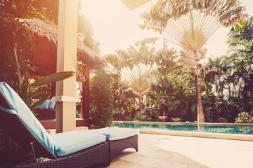 Lounger near villa swimming pool with palm trees view