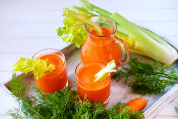 Fresh carrot juice poured into glasses and green celery