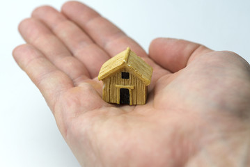 Hand holding a house.
