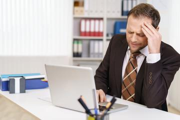 mann sitzt am arbeitsplatz und ärgert sich