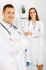 Two confident doctors standing at the office.