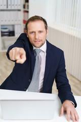 mann im büro zeigt nach vorne