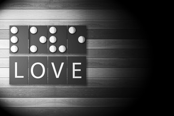 Black and White Photo of Braille Alphabet meaning of LOVE in Bright Light on wooden Background.