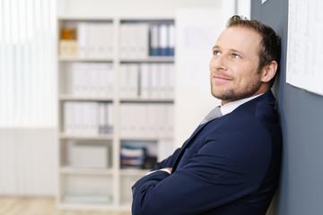 entspannter geschäftsmann lehnt an der wand im büro