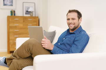 glücklicher mann mit laptop auf dem sofa