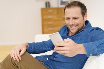 entspannter mann nutzt sein handy zuhause
