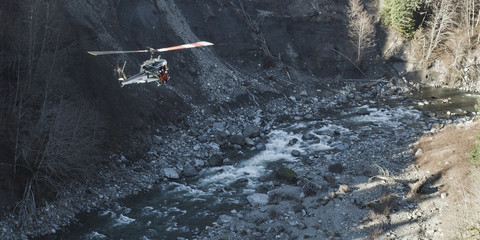 A helicopter flying above a rocky river bed in a valley.