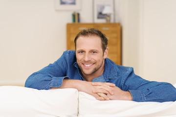 lächelnder mann sitzt zuhause auf dem sofa