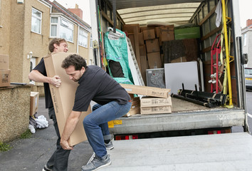 Removals business. Two men lifting an awkward package onto a van.