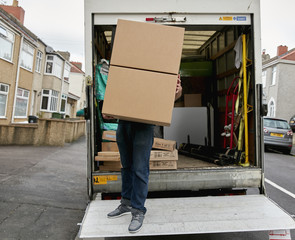 Removals business. A man on the tailgate of a van carrying a large box.