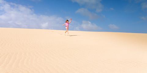 jolie fille bondissant dans le sable