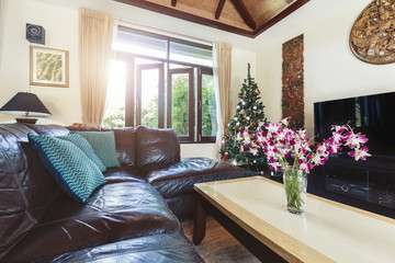 living room interior in luxury villa: sofa, tv, open window, tropical orchid flowers, summer