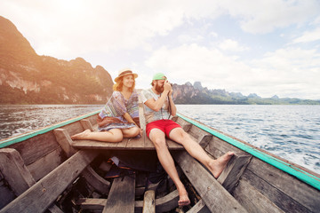 Funny couple: man with a beard and woman wearing hat traveling by boat on tropical mountain lake. Summer travel, family vacation